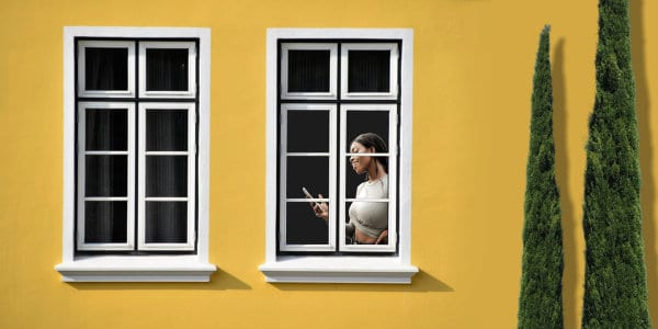 Woman behind window talking on phone