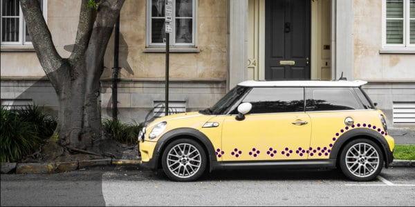 Yellow parked Mini Cooper car with purple polka dots