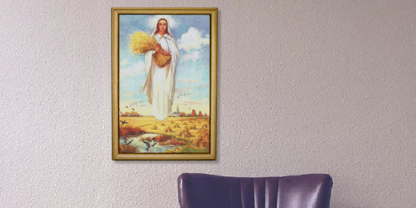 Framed picture of Our Lady of the Prairies hanging above chair