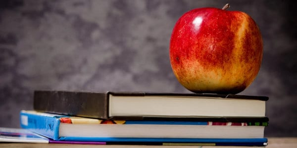 close-up of apple on top of books
