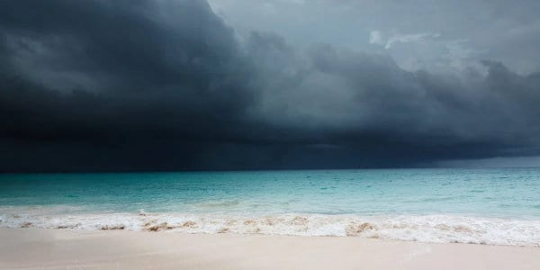 Advancing storm with dark clouds over tropical beach