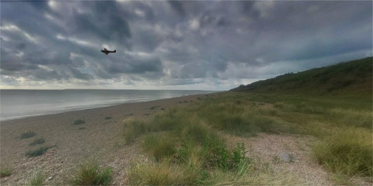 WWII fighter plane flying over North Sea at Suffolk beach